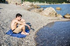 Hombre joven hermoso en la playa en un día soleado Fotos de archivo libres de regalías