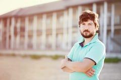 Hombre joven hermoso en la playa, hotel en el fondo Imágenes de archivo libres de regalías
