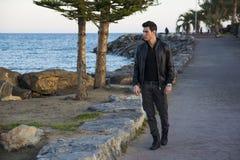 Hombre joven hermoso en la playa a lo largo de la orilla Fotografía de archivo libre de regalías