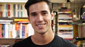 Hombre joven hermoso en la sonrisa de la librería almacen de video