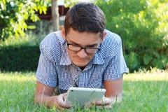 Hombre joven hermoso en los vidrios que miran la tableta al aire libre Foto de archivo libre de regalías