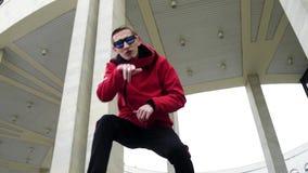 Hombre joven hermoso en rap rojos de la chaqueta y de las gafas de sol al lado de columnas del granito metrajes