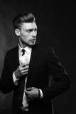Hombre joven hermoso en traje en fondo oscuro con Fotografía de archivo