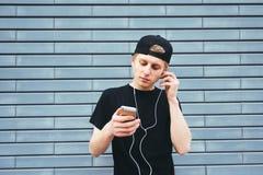 Hombre joven hermoso en un casquillo y una camisa negra que escucha la música en los auriculares con su teléfono Imagen de archivo