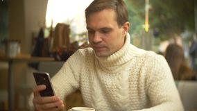 Hombre joven hermoso en un suéter blanco usando un smartphone, sentándose en un café en la ciudad en contra una ventana fotos de archivo