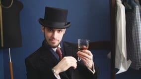 Hombre joven hermoso en un whisky de consumición del traje clásico en restaurante metrajes