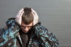 Hombre joven hermoso Llevar a cabo su cabeza, dolor de cabeza foto de archivo libre de regalías