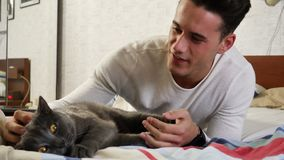 Hombre joven hermoso que abraza a su Gray Cat Pet almacen de metraje de vídeo
