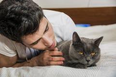 Hombre joven hermoso que abraza a su Gray Cat Pet Foto de archivo
