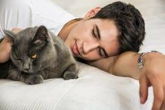 Hombre joven hermoso que abraza a su Gray Cat Pet Imágenes de archivo libres de regalías