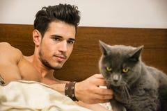Hombre joven hermoso que abraza a su Gray Cat Pet Fotografía de archivo libre de regalías