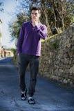 Hombre joven hermoso que camina a lo largo del camino rural Imagenes de archivo