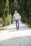 Hombre joven hermoso que camina a lo largo del camino rural Foto de archivo libre de regalías