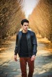 Hombre joven hermoso que camina a lo largo del camino rural Fotografía de archivo libre de regalías