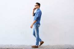 Hombre joven hermoso que camina y que habla en el teléfono celular Imagen de archivo libre de regalías