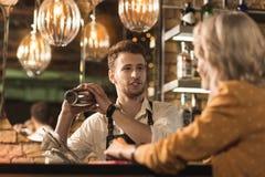 Hombre joven hermoso que charla mientras que hace el cóctel Fotografía de archivo libre de regalías