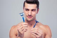 Hombre joven hermoso que elige la maquinilla de afeitar Fotos de archivo