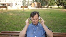 Hombre joven hermoso que escucha la música de su smartphone con los auriculares, bailando afuera en el parque en un banco en almacen de video