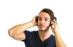 Hombre joven hermoso que escucha la música en los auriculares imagen de archivo
