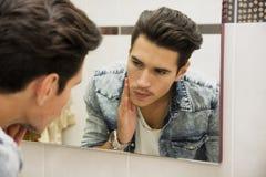 Hombre joven hermoso que examina su piel de la cara en espejo del cuarto de baño Foto de archivo libre de regalías