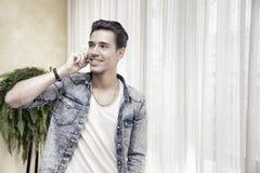 Hombre joven hermoso que habla en el teléfono en casa que sonríe imágenes de archivo libres de regalías