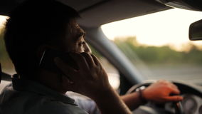 Hombre joven hermoso que habla en el teléfono móvil mientras que conduce su coche Malos hábitos del conductor aventurado, imprude metrajes