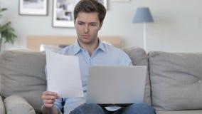 Hombre joven hermoso que hace papeleo mientras que se sienta en espacio de trabajo creativo almacen de metraje de vídeo