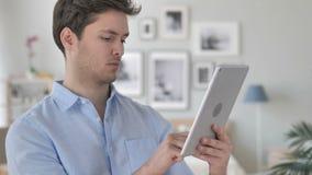 Hombre joven hermoso que hojea en la tableta almacen de video