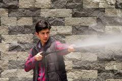 Hombre joven hermoso que lleva el rojo cuadrado del modelo que sostiene el arma de agua de alta presión, en un fondo gris de la p Foto de archivo libre de regalías