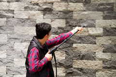 Hombre joven hermoso que lleva el rojo cuadrado del modelo que sostiene el arma de agua de alta presión, señalando hacia la pared Imagenes de archivo