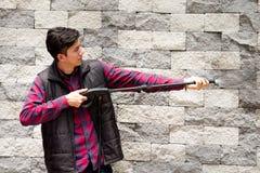 Hombre joven hermoso que lleva el rojo cuadrado del modelo que sostiene el arma de agua de alta presión, señalando hacia la pared Fotos de archivo libres de regalías
