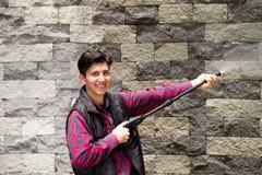 Hombre joven hermoso que lleva el rojo cuadrado del modelo que sostiene el arma de agua de alta presión, señalando hacia la pared Imagen de archivo