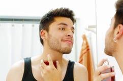 Hombre joven hermoso que lleva la mirada superior de la camiseta negra en el espejo, aplicando cologne durante concepto de la rut Imagenes de archivo
