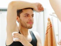 Hombre joven hermoso que lleva la mirada superior de la camiseta negra en el espejo, aplicando el desodorante durante concepto de Imágenes de archivo libres de regalías
