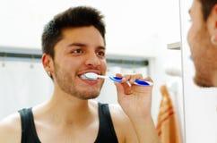 Hombre joven hermoso que lleva la mirada superior de la camiseta negra en el espejo que sonríe mientras que cepilla los dientes Fotos de archivo