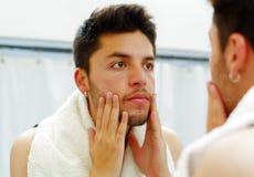 Hombre joven hermoso que lleva la mirada superior de la camiseta negra en el espejo, tocando sus mejillas durante concepto de la  Fotos de archivo libres de regalías