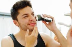 Hombre joven hermoso que lleva la mirada superior de la camiseta negra en espejo, usando la máquina de afeitar eléctrica durante  Foto de archivo libre de regalías