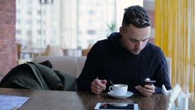 Hombre joven hermoso que manda un SMS en smartphone en café metrajes