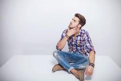 Hombre joven hermoso que piensa mientras que mira para arriba Imagen de archivo
