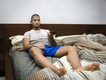 Hombre joven hermoso que pone en su cama que ve la TV Fotos de archivo libres de regalías
