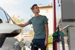 Hombre joven hermoso que reaprovisiona el coche de combustible en un día soleado imágenes de archivo libres de regalías
