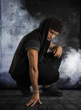 Hombre joven hermoso que se arrodilla abajo en sudadera con capucha oscura en fondo negro Imagenes de archivo