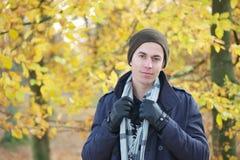 Hombre joven hermoso que se coloca al aire libre con la bufanda y los guantes del sombrero de la chaqueta Imagenes de archivo