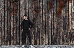 Hombre joven hermoso que se coloca cerca de una pared de madera Imagen de archivo libre de regalías
