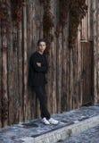 Hombre joven hermoso que se coloca cerca de una pared de madera Fotos de archivo libres de regalías