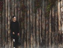 Hombre joven hermoso que se coloca cerca de una pared de madera Imagen de archivo