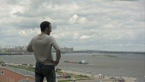 Hombre joven hermoso que se coloca cerca del río y que mira adelante almacen de video