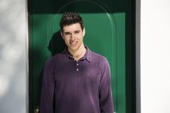 Hombre joven hermoso que se coloca delante de puerta de la casa Fotos de archivo