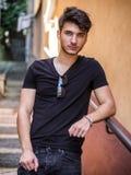 Hombre joven hermoso que se coloca en calle europea de la ciudad imagen de archivo libre de regalías