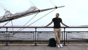 Hombre joven hermoso que se coloca en el embarcadero, cerca de la cerca cerca del bauprés de la nave y mirando alrededor metrajes